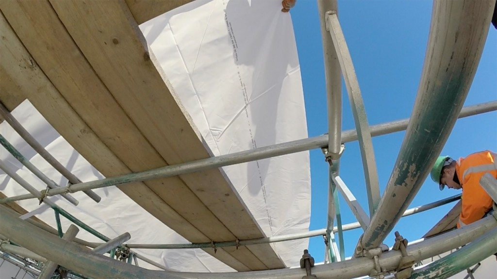 pulling the shrink wrap roof sheet across